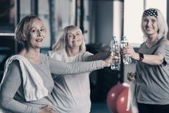 使瓶互相的水叮当响的三名微笑的妇女 免版税库存图片