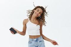 使生活的音乐五颜六色 无忧无虑的迷人的深色皮肤的女孩画象有跳跃和跳舞微笑的dreadlocks的 免版税图库摄影