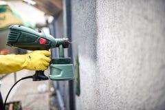 使用一个专业喷枪,供以人员工作者有灰色油漆的绘画墙壁 人使用防护手套的绘画墙壁 免版税库存照片