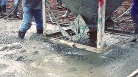 使用一个具体钢篮子的人工作者为水泥在倾吐预拌混凝土以后 股票录像