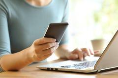 使用一个巧妙的电话和一台膝上型计算机的女孩手在书桌上 免版税库存图片