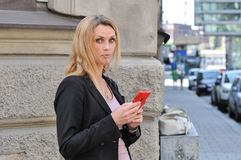 使用一个巧妙的电话的一个年轻女商人户外 库存照片