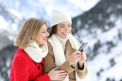 使用一个巧妙的电话的两个朋友在山的冬天 库存图片