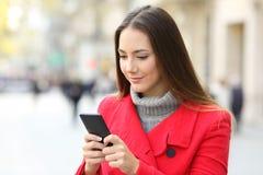 使用一个巧妙的电话的严肃的妇女在冬天 免版税库存照片