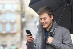 使用一个巧妙的电话的人在一个雨天 免版税库存照片