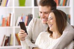 使用一个巧妙的电话的夫妇在家在冬天 库存图片