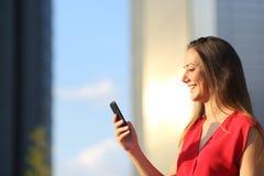 使用一个巧妙的电话的女商人 免版税库存照片