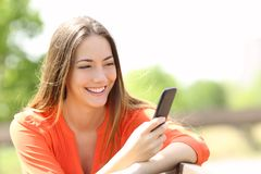 使用一个巧妙的电话的女孩在夏天 免版税图库摄影