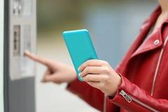 使用一个巧妙的电话的女孩支付在付款机器 免版税库存照片