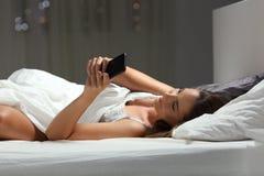 使用一个巧妙的电话的妇女在床上的夜 库存图片