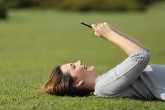 使用一个巧妙的电话的妇女基于草在公园 免版税库存照片