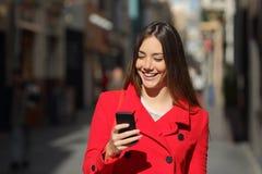 使用一个巧妙的电话的妇女,当步行在街道时 库存照片