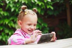 使用一个巧妙的电话的小孩女孩 免版税库存图片