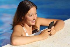 使用一个巧妙的电话的愉快的女孩在一个游泳池在暑假 免版税库存照片
