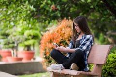 使用一个巧妙的电话的愉快的女孩在城市公园坐长凳 库存照片