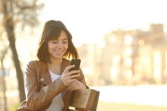 使用一个巧妙的电话的愉快的女孩在城市公园 免版税库存照片