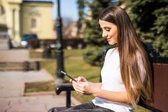 使用一个巧妙的电话的愉快的女孩在城市坐长凳 免版税图库摄影