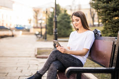 使用一个巧妙的电话的愉快的女孩在城市坐长凳 免版税库存图片