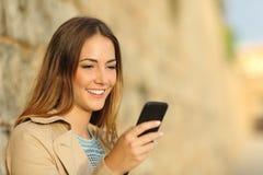 使用一个巧妙的电话的愉快的妇女在一个老镇 免版税库存图片