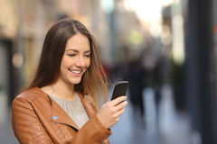 使用一个巧妙的电话的愉快的妇女在街道 库存照片