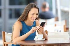 使用一个巧妙的电话的愉快的妇女在酒吧大阳台 免版税图库摄影