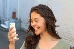使用一个巧妙的电话的愉快的少妇在街道有采取selfie或使用Skype或做录影的未聚焦的背景 免版税库存图片