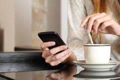 使用一个巧妙的电话的手在早餐期间在家 免版税库存照片