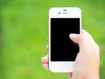 使用一个巧妙的电话的手以绿色 免版税库存图片