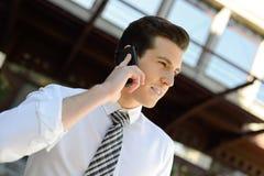 使用一个巧妙的电话的生意人在办公楼 库存照片