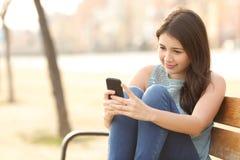 使用一个巧妙的电话的青少年的女孩坐在长凳 免版税库存图片