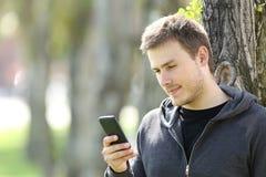 使用一个巧妙的电话的青少年的男孩户外 图库摄影
