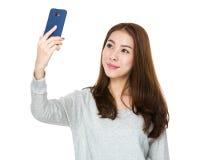 使用一个巧妙的电话的年轻亚裔妇女为自已照片 免版税库存照片