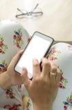 使用一个巧妙的设备电话的妇女在表模板 免版税库存照片