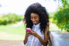 使用一个手机的一个少年黑人女孩的室外画象- 库存照片