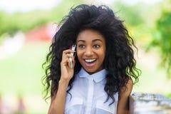 使用一个手机的一个少年黑人女孩的室外画象- 免版税库存照片