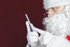使用一个手机的圣诞老人在圣诞节时间 库存照片
