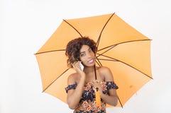 使用一个手机的妇女在伞下 库存图片