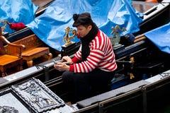 使用一个手机的平底船的船夫,当等待客户时 图库摄影