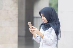 使用一个手机的年轻回教妇女 免版税库存图片