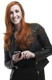 使用一个手机的微笑的红头发人妇女 免版税库存图片