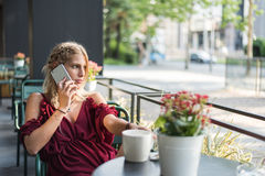 使用一个手机的愉快的白肤金发的美丽的妇女喝杯子 免版税图库摄影