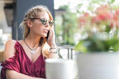 使用一个手机的愉快的白肤金发的美丽的妇女喝杯子 库存照片