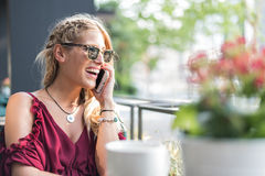 使用一个手机的愉快的白肤金发的美丽的妇女喝杯子 免版税库存照片