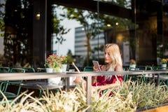 使用一个手机的愉快的白肤金发的美丽的妇女喝杯子 库存图片