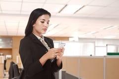 使用一个手机的年轻亚裔女商人 免版税库存照片