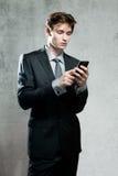 使用一个手机的年轻商人 免版税库存照片