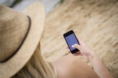 使用一个手机,妇女坐海滩 免版税库存照片
