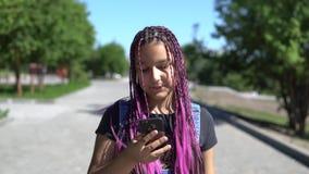 使用一个手机,有长的猪尾的一个美丽的女孩在公园走 股票视频