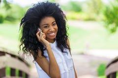 使用一个手机-非洲人民的少年黑人女孩 库存图片