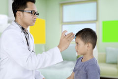 使用一个数字体温计的儿科医生为患者 免版税库存照片